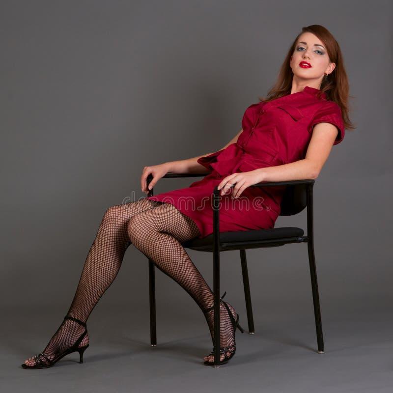 Redheadmädchen, das auf einem Stuhl sich entspannt stockfotografie