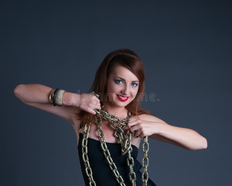 Redheadmädchen in den goldenen Ketten lizenzfreies stockfoto