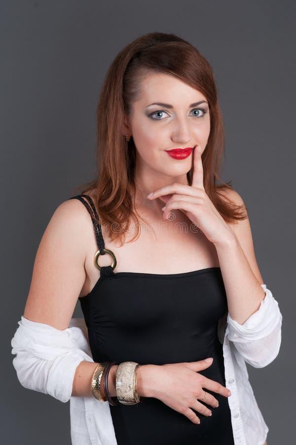 Redheadmädchen-Holdingfinger zu ihren Lippen stockfotografie