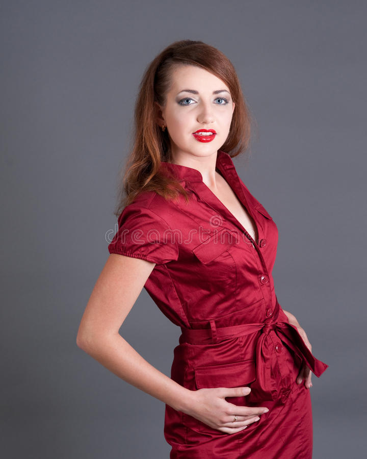 Redheadmädchen im roten Kleid stockfoto