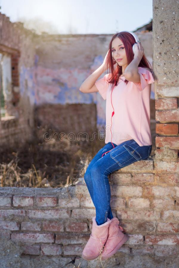 Redheads female listening to music on headphones on ruins wall red bricks of retro house in sunset royalty free stock photos