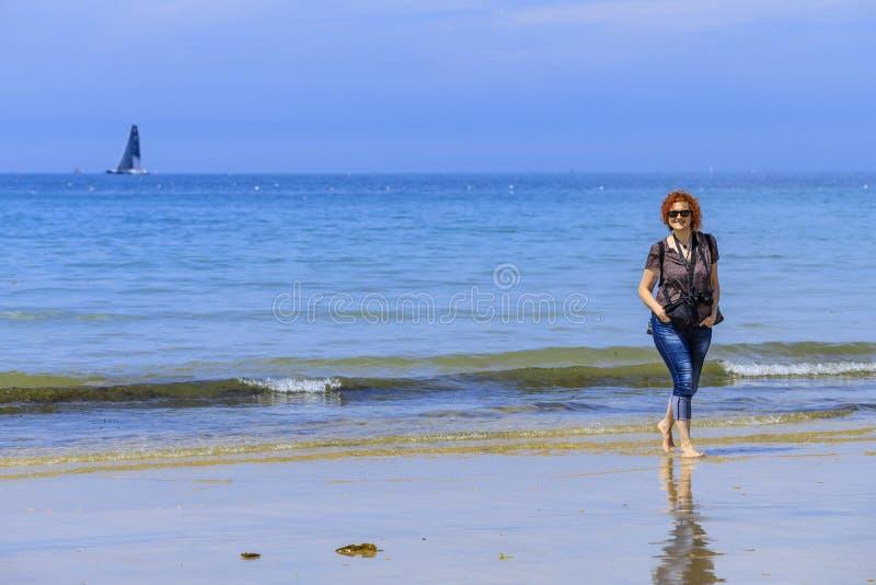 Redhedvrouw op de kust stock fotografie