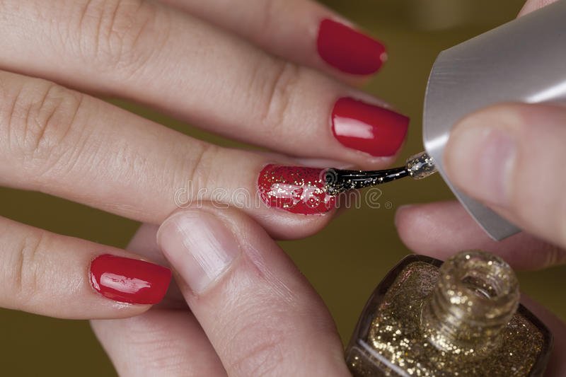 Redn finger nails with a golden sparks stock photo