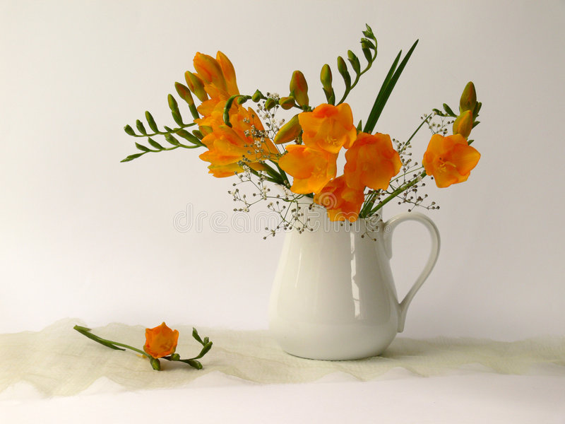 Redolent. Yellow fragrances flowers in white jug royalty free stock image
