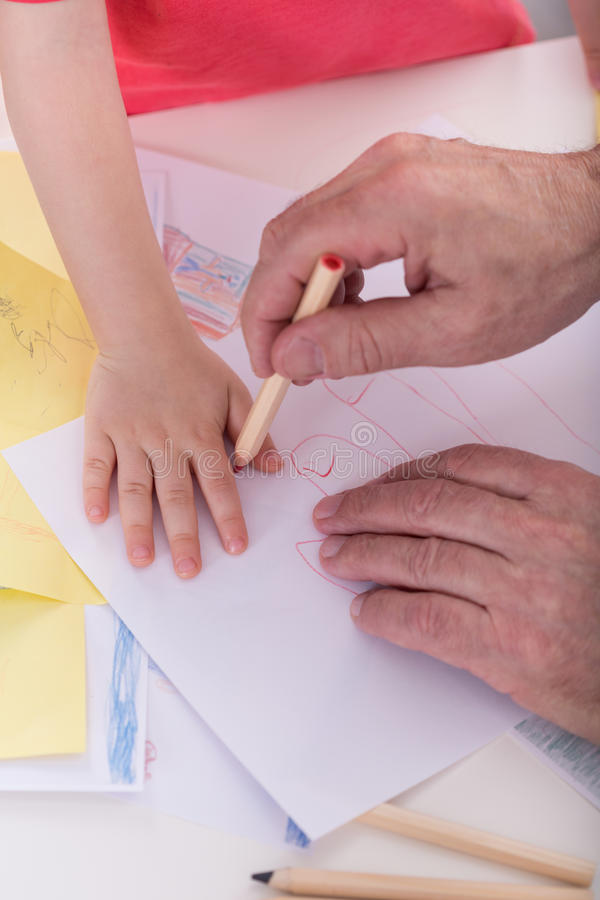 Redrawing boy's hand. Close-up of senior grandfather redrawing boy's hand stock images
