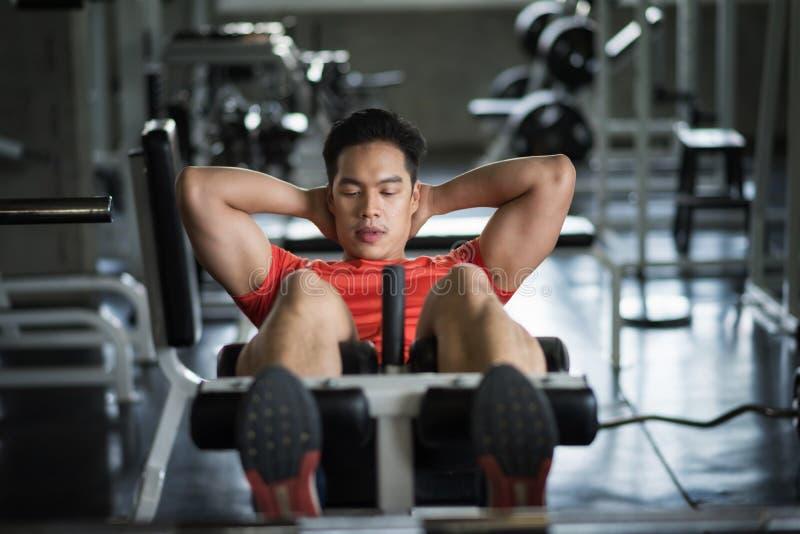 Redressement assis d'homme dans le gymnase de forme physique pour le bodybuilding images libres de droits