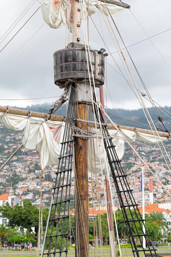 Redskap av en gammal segla skyttel - en mast, en mast, lyftt r?d-vit seglar, rep arkivfoton