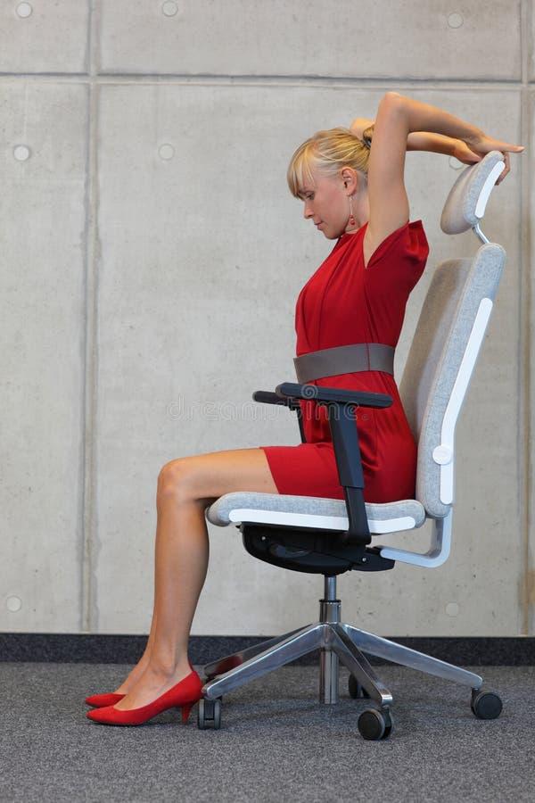 Redução da tensão no trabalho de escritório - mulher que exercita na cadeira fotografia de stock