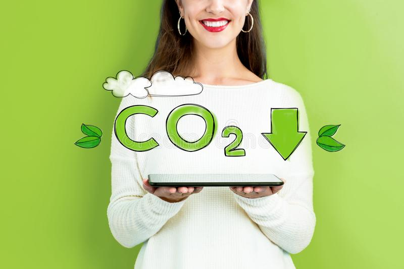 Reduce CO2 with woman holding a tablet stock image
