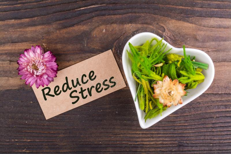 Reduce stress. On card with dried flower and heart shape bowl on wood stock photos