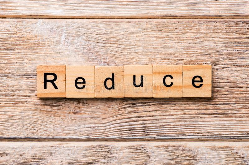Reduce word written on wood block. reduce text on wooden table for your desing, concept royalty free stock photography