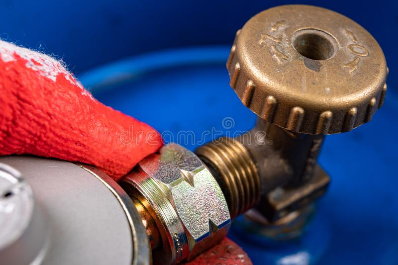 Reducer and gas cylinder for domestic use. Replacing the gas cylinder in the home kitchen stock photo