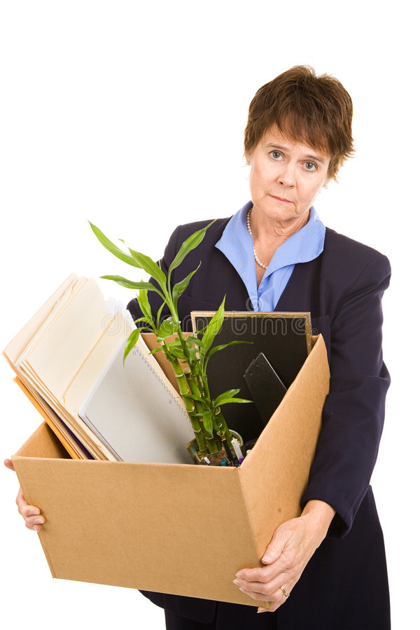 Redundant. Middle aged woman laid off from her white collar job carries a box of her belongings. Isolated on white stock images