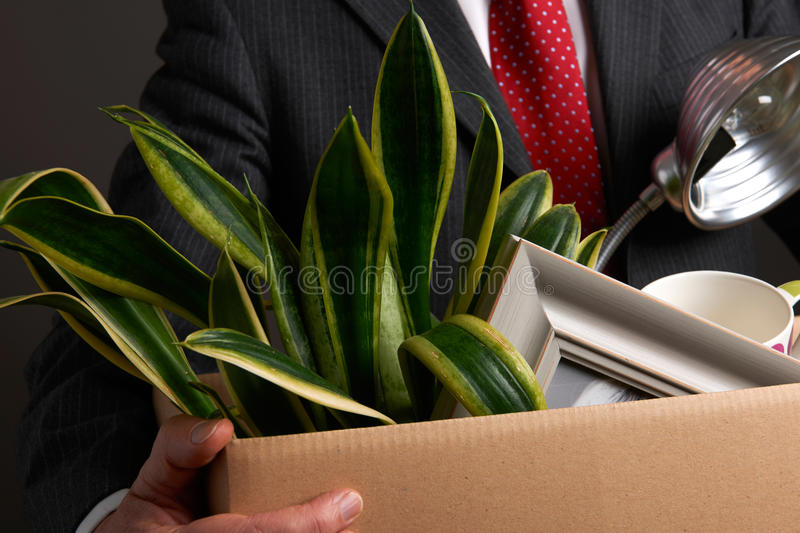 Redundant Businessman With Possessions In Box. Studio Shot Of Redundant Businessman With Possessions In Box stock photo