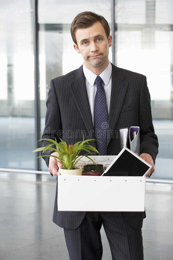 A redundant businessman taking his belongings home in a box royalty free stock image