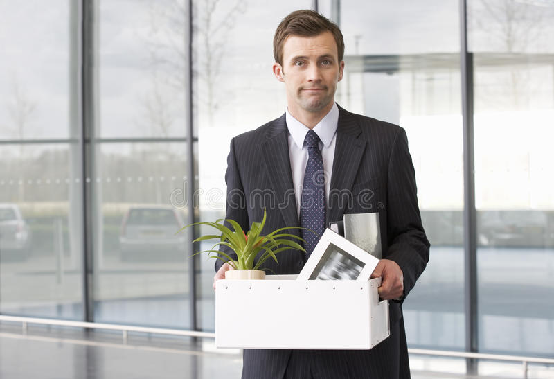 A redundant businessman taking his belongings home in a box royalty free stock photos
