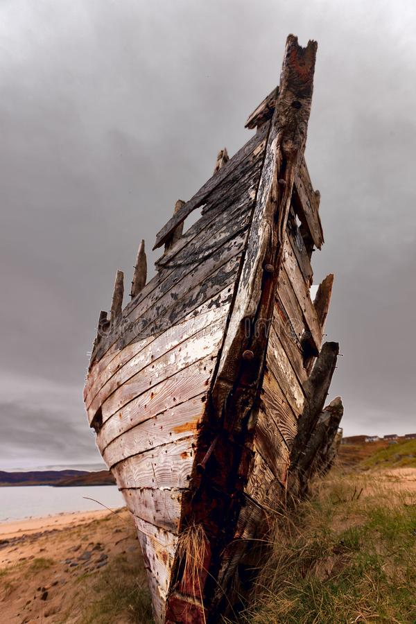 Redundant. The wreck of an old fisher boat on the sandy beach of Melness in north Scotland close to the little harbour for the local fisherman. The old boat is stock photography
