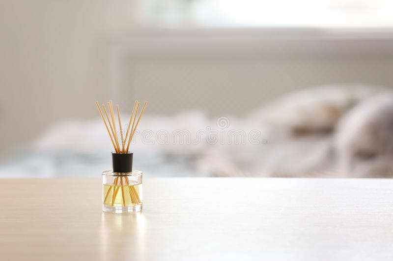 Reed air freshener on table against blurred background. Aromatic reed air freshener on table against blurred background stock photo