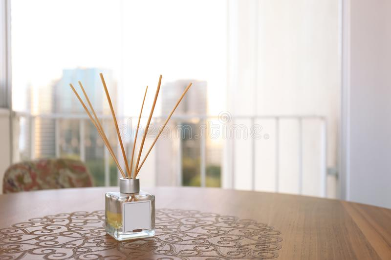 Reed air freshener on wooden table. In room stock photo