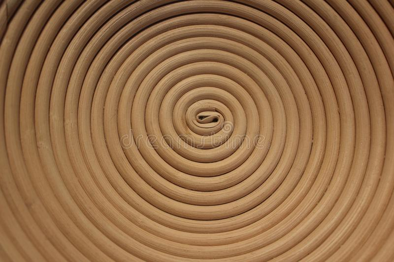 Reed basket hypnotic swirl. A photo of the bottom of a reed basket. It looks like a hypnotic swirl stock images