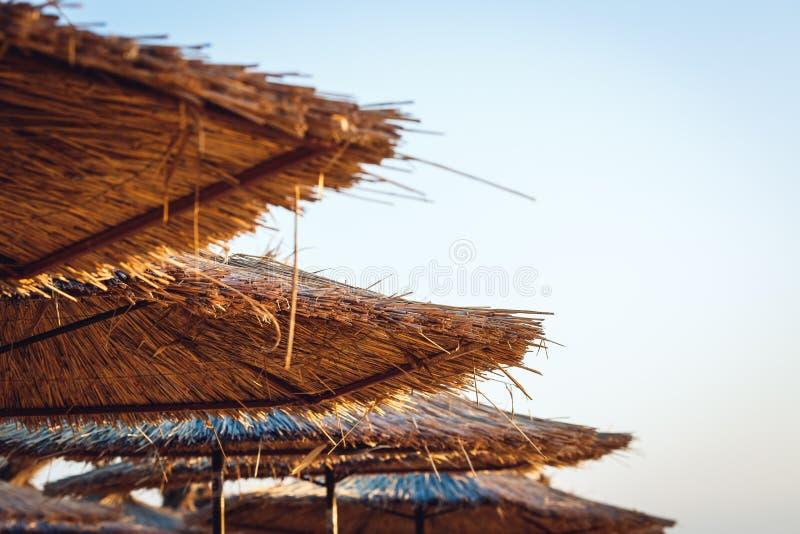 Reed beach umbrellas against blue sky. stock photos