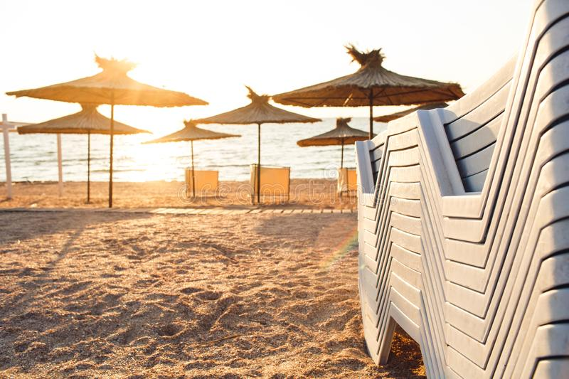 Reed beach umbrellas and sunbeds on sandy seashore in sun. royalty free stock image