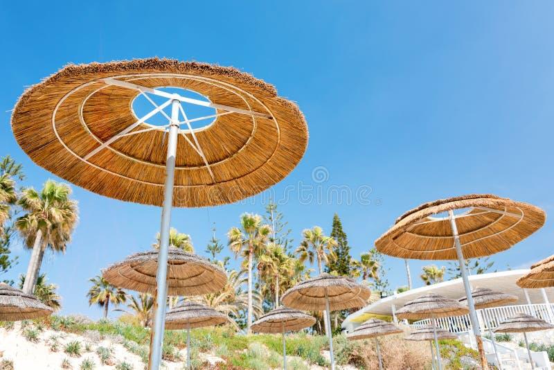 Reed beach umbrellas, sunshades against blue sky on the beach. Bamboo parasols, straw umbrellas on on white sandy. Tropical seashore. Tropical sea beach stock photos