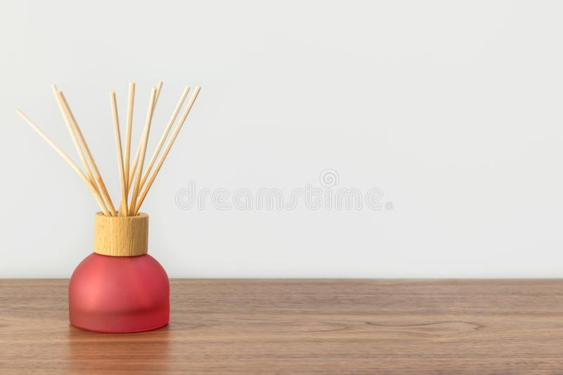 Reed diffuser with scented oil bamboo sticks in red glass bottle on wooden table white wall background. Aromatherapy home interior stock image