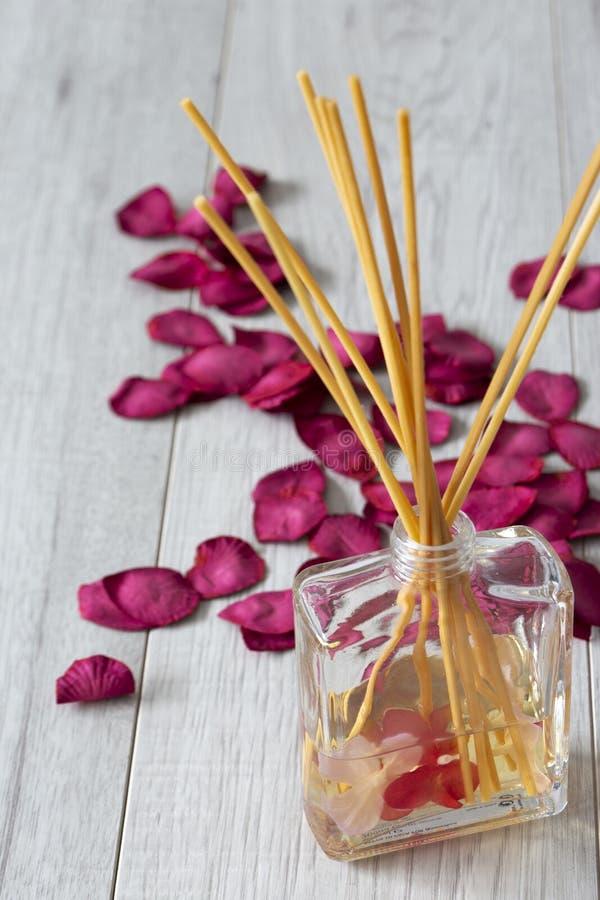 REEDdiffusor mit Duft in einem Glasgef?? mit den rosafarbenen Blumenbl?ttern stockfotografie