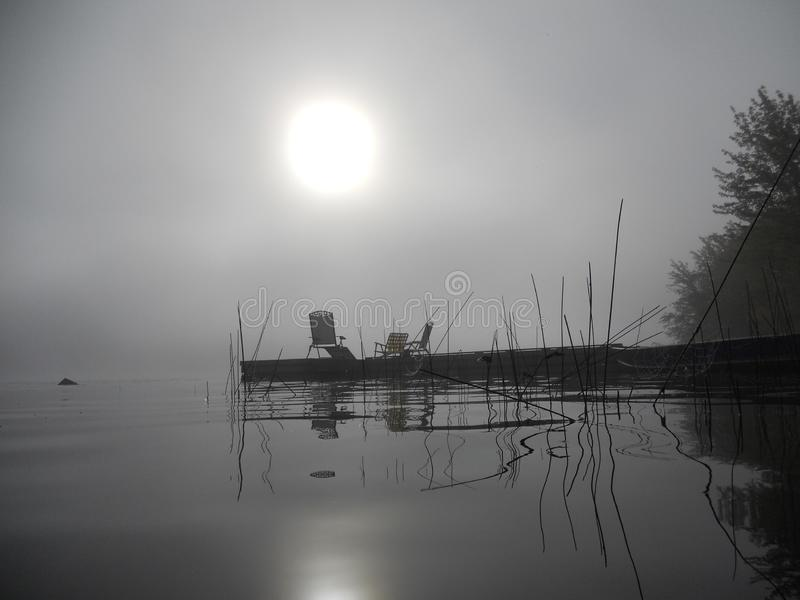 Reeds and jetty reflecting in the water on a misty morning stock image