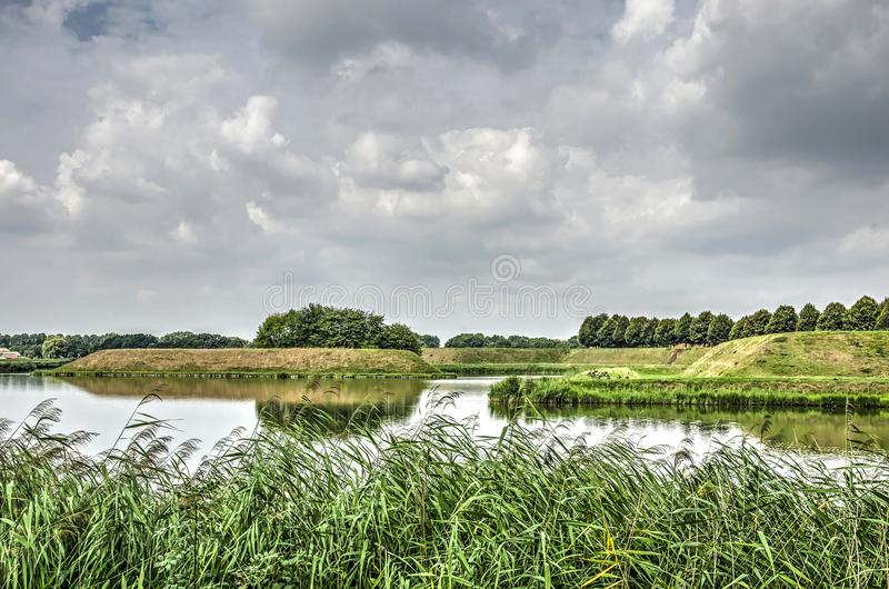Reeds and ramparts. View across a bank with reeds towards the moats and ramparts around the fortified town of Leusden, The Netherlands royalty free stock image