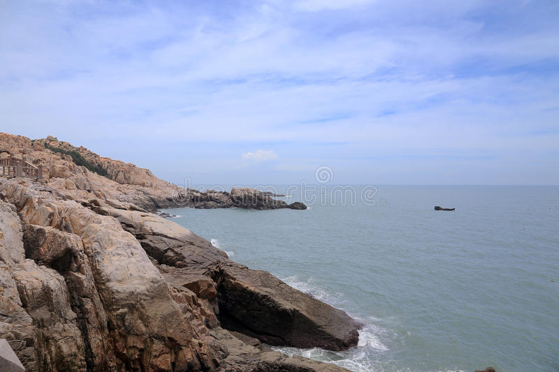 Reef rock in the coast of meizhou island. Calm beach, blue sky and white clouds , putian city ,fujian province , china stock photo