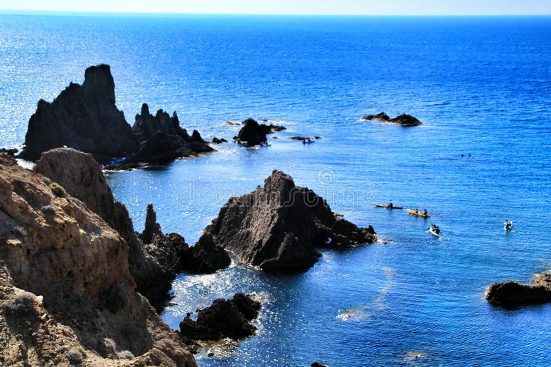 Reef of the Sirens in Cabo de Gata, Almeria, Spain. In a sunny day of summer. People practicing canoeing in the background royalty free stock image