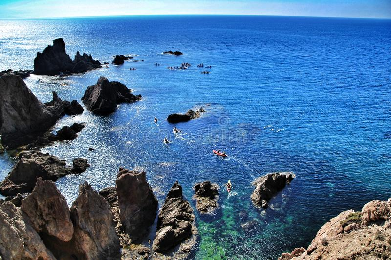 Reef of the Sirens in Cabo de Gata, Almeria, Spain. In a sunny day of summer. People practicing canoeing in the background royalty free stock photography