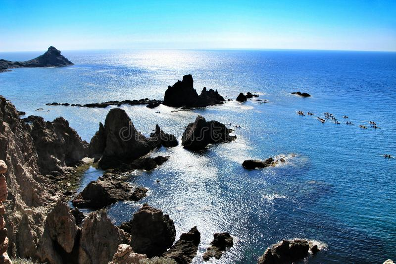 Reef of the Sirens in Cabo de Gata, Almeria, Spain. In a sunny day of summer. People practicing canoeing in the background royalty free stock photo
