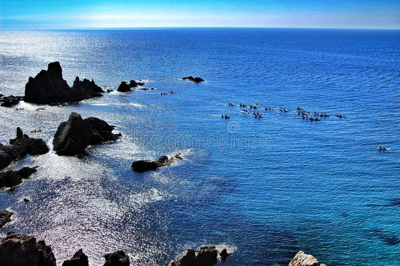 Reef of the Sirens in Cabo de Gata, Almeria, Spain. In a sunny day of summer. People practicing canoeing in the background stock photography