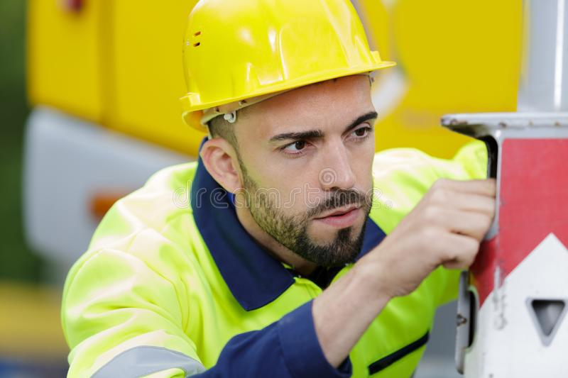 Reefer container technician repairing machinery. Reefer container technician is repairing machinery stock photo