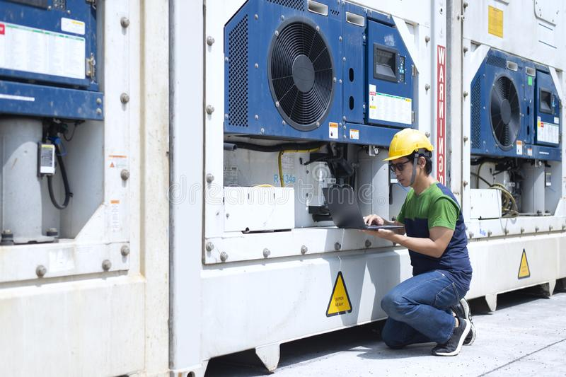 Reefer technician is taking care of reefer container at the port while working with tablet to monitor Frozen and Chill. Cargo royalty free stock image