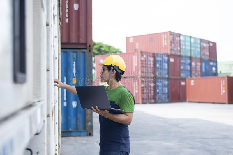 Reefer technician is taking care of reefer container at the port while working with tablet to monitor Frozen and Chill. Cargo stock photo
