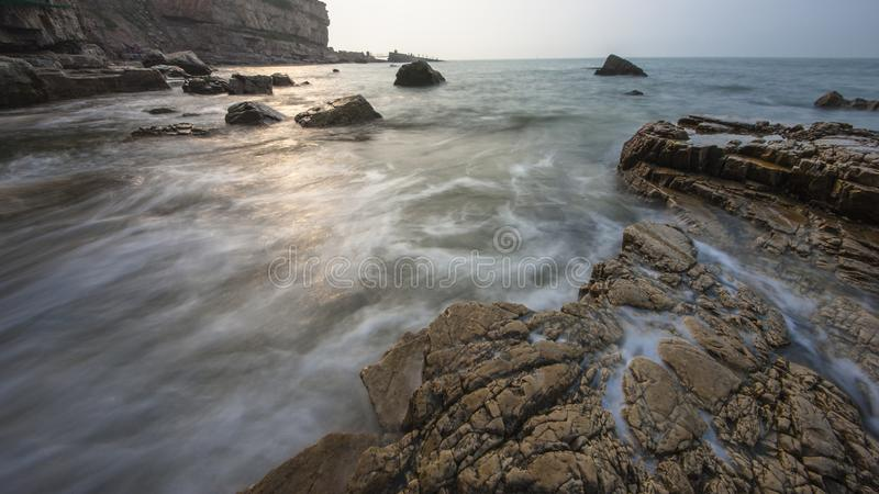 Reefs and waves. Jiaodong Peninsula is located in the northeast coastal area of China`s North China Plain, east of Shandong Province, hilly land, north of Bohai royalty free stock images