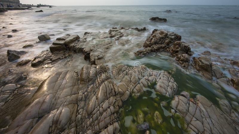 Reefs and waves. Jiaodong Peninsula is located in the northeast coastal area of China`s North China Plain, east of Shandong Province, hilly land, north of Bohai stock photography