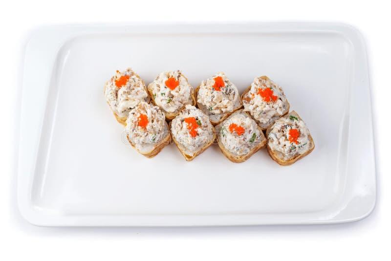 Reeks broodjes in twee rijen op een rechthoekige plaat op een witte achtergrond stock foto's