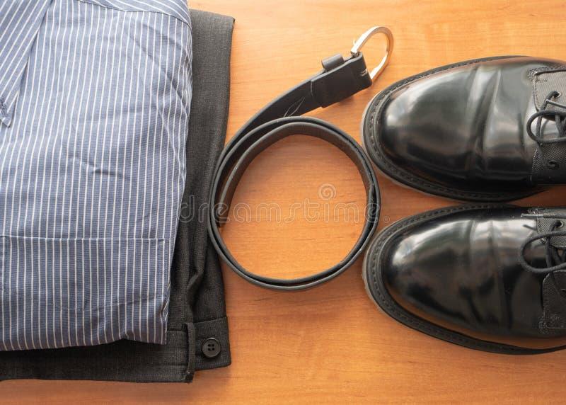 Reeks de slijtagekleren van de mensenzakenman op een bureau - paar van zwarte schoenen, broek, overhemd en leerriem royalty-vrije stock afbeeldingen