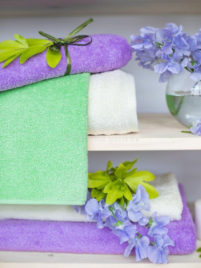 Reeks de verschillende handdoeken van de kleurenbadstof met blauwe bloemen en kaarsen op houten shelfs royalty-vrije stock afbeelding