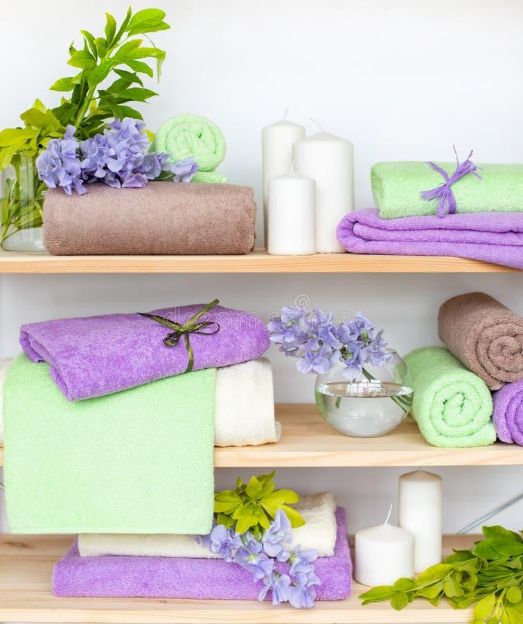 Reeks de verschillende handdoeken van de kleurenbadstof met blauwe bloemen en kaarsen op houten shelfs royalty-vrije stock foto's
