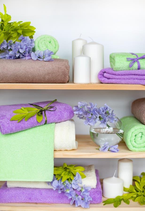Reeks de verschillende handdoeken van de kleurenbadstof met blauwe bloemen en kaarsen op houten shelfs royalty-vrije stock fotografie