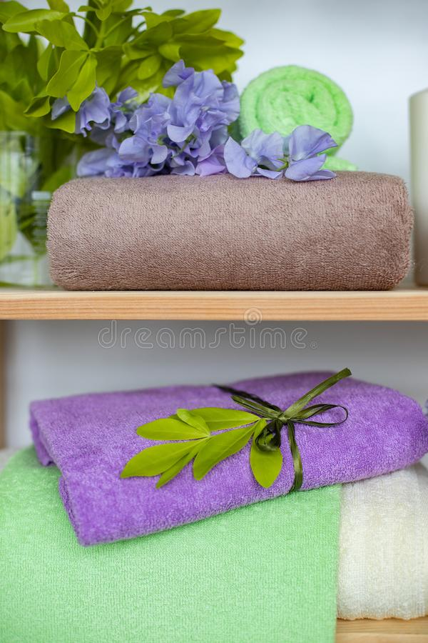Reeks de verschillende handdoeken van de kleurenbadstof met blauwe bloemen en kaarsen op houten shelfs stock afbeeldingen