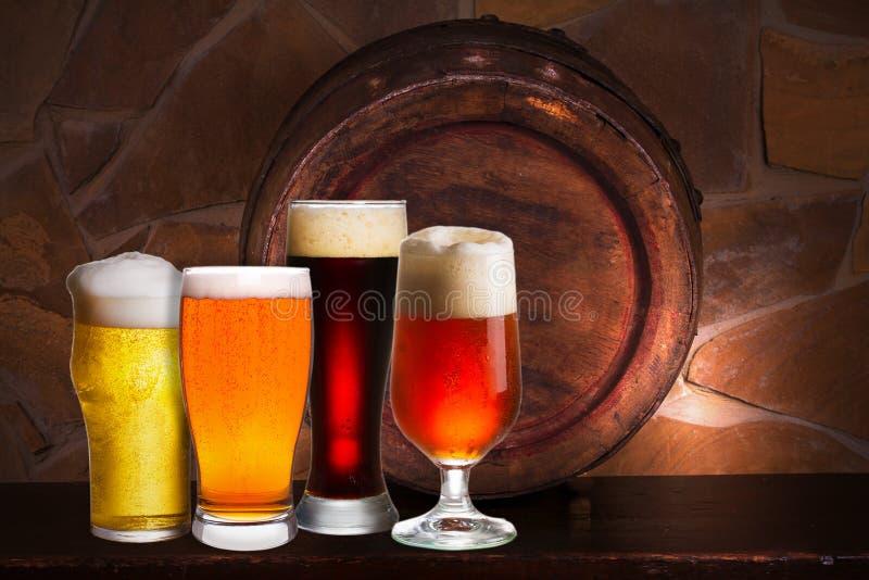 Reeks diverse glazen bier in kelder, bar of restaurant Bierglazen, oude biervat en bakstenen muur op achtergrond stock foto