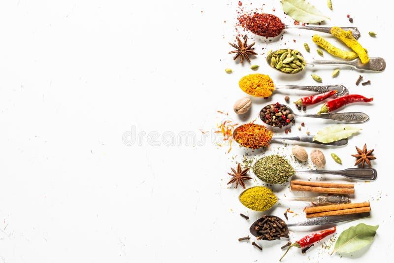 Reeks diverse kruiden in lepels op wit stock foto