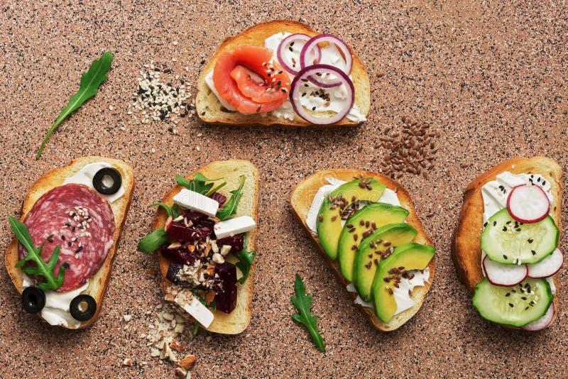 Reeks een verscheidenheid van sandwiches met zalm, worst, avocado, biet, feta-kaas, komkommer en radijs op een steen bruine achte stock foto's